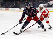 Columbus Blue Jackets forward Cam Atkinson, left, controls the puck in front of Detroit Red Wings forward Luke Glendening during the second period of an NHL hockey game in Columbus, Ohio, Saturday, May 8, 2021. (AP Photo/Paul Vernon)