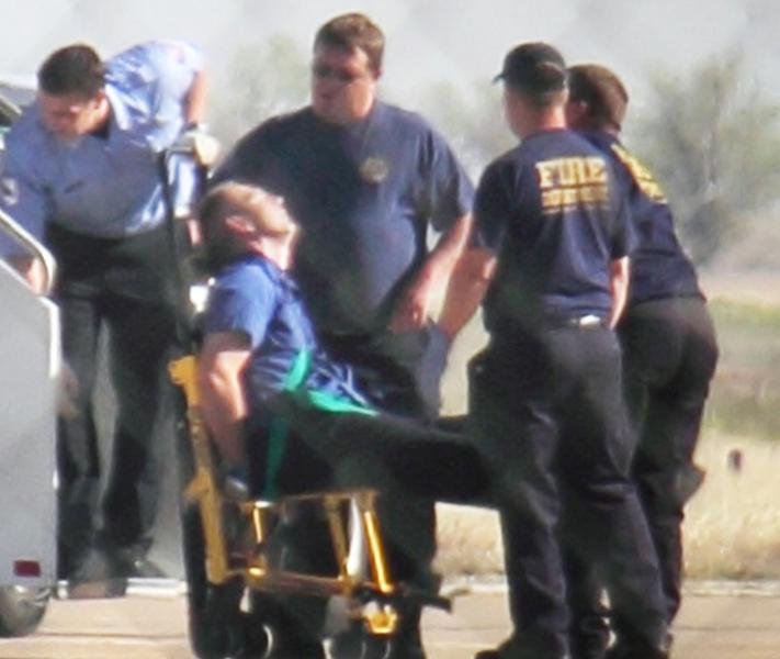 "Emergency workers tend to a JetBlue captain that had a ""medical situation"" during a Las Vegas-bound flight from JFK International airport, Tuesday, March 27, 2012, in Amarillo, Texas. Passengers said the pilot screamed that Iraq or Afghanistan had planted a bomb on the flight, was locked out of the cockpit, and then tackled and restrained by passengers. The pilot who subsequently took command of the aircraft elected to land in Amarillo at about 10 a.m., JetBlue Airways said in a statement. (AP Photo/Steve Douglas)"