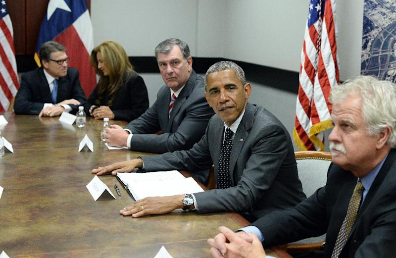 US President Barack Obama (2nd-R) and Texas Governor Rick Perry (L) sits in a meeting with local elected officials and faith leaders in Dallas, Texas, on July 9, 2014 to discuss the urgent humanitarian situation at the Southwest border (AFP Photo/Jewel Samad)