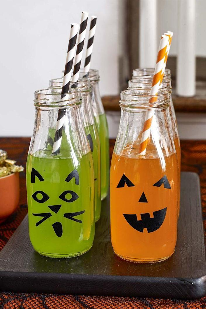 """<p>All it takes is a little contact paper and a savvy template to turn mini milk bottles into festive drinking vessels for your party.</p><p><em><strong><a href=""""https://www.womansday.com/home/crafts-projects/g22840971/halloween-2018-templates/"""" rel=""""nofollow noopener"""" target=""""_blank"""" data-ylk=""""slk:Get the Bottle Beverages template"""" class=""""link rapid-noclick-resp"""">Get the Bottle Beverages template</a>.</strong></em></p><p><strong><a class=""""link rapid-noclick-resp"""" href=""""https://www.amazon.com/QAPPDA-Breakfast-Container-Drinking-Chalkboard/dp/B07K7732NW/ref=sr_1_5?crid=3TIKLSLDKDSI8&dchild=1&keywords=glass+milk+bottle&qid=1626438973&s=home-garden&sprefix=glass+milk%2Cgarden%2C157&sr=1-5&tag=syn-yahoo-20&ascsubtag=%5Bartid%7C10070.g.1908%5Bsrc%7Cyahoo-us"""" rel=""""nofollow noopener"""" target=""""_blank"""" data-ylk=""""slk:SHOP MINI MILK BOTTLES"""">SHOP MINI MILK BOTTLES</a><br></strong></p>"""
