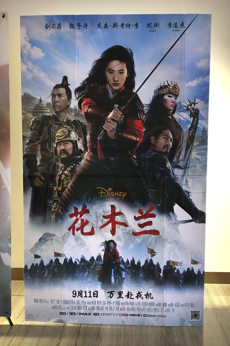 """A poster for the Disney movie """"Mulan"""" is displayed at a movie theater in Beijing on Sept. 11, 2020. The remake of """"Mulan"""" struck all the right chords to be a hit in the key Chinese market. Disney cast beloved actresses Liu Yifei as Mulan and removed a popular dragon sidekick in the original to cater to Chinese tastes. (AP Photo/Mark Schiefelbein)"""