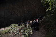 """Members of the French team that participated in the """"Deep Time"""" study, emerge from the Lombrives Cave after 40 days underground in Ussat les Bains, France, Saturday, April 24, 2021. After 40 days in voluntary isolation, 15 people participating in a scientific experiment have emerged from a vast cave in southwestern France. Eight men and seven women lived in the dark, damp depths of the Lombrives cave in the Pyrenees to help researchers understand how people adapt to drastic changes in living conditions and environments. They had no clocks, no sunlight and no contact with the world above. (AP Photo/Renata Brito)"""