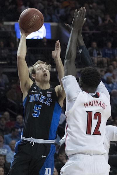 Duke guard Luke Kennard (5) shoots over Louisville forward Mangok Mathiang (12) during the first half of an NCAA college basketball game in the Atlantic Coast Conference tournament, Thursday, March 9, 2017, in New York. (AP Photo/Mary Altaffer)