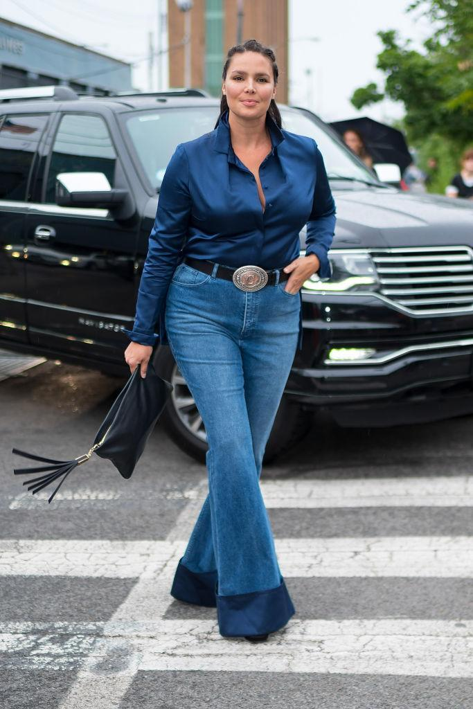 """<p>Model Candice Huffine wears a<a href=""""https://11honore.com/products/brandon-maxwell-navy-rolled-collar-satin-shirt"""" rel=""""nofollow noopener"""" target=""""_blank"""" data-ylk=""""slk:navy blouse"""" class=""""link rapid-noclick-resp""""> navy blouse</a> and<a href=""""https://11honore.com/products/brandon-maxwell-blue-bell-bottom-denim"""" rel=""""nofollow noopener"""" target=""""_blank"""" data-ylk=""""slk:jeans"""" class=""""link rapid-noclick-resp""""> jeans</a> by Brandon Maxwell from 11 Honoré ahead of the designer's NYFW show. (Photo: Getty) </p>"""