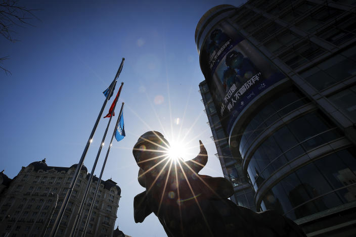 A statue of a bull, an investment icon, stands outside an office building with a screen showing propaganda about fighting against Coronavirus in Beijing, Tuesday, March 10, 2020. Asian stock markets took a breather from recent steep declines on Tuesday, with several regional benchmarks gaining more than 1% after New York futures reversed on news that President Donald Trump plans to ask Congress for a tax cut and other quick measures to ease the pain of the virus outbreak. (AP Photo/Andy Wong)