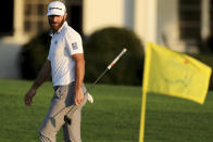 Dustin Johnson looks over his shot on the 18th green next to the Masters yellow flag during the third round of the Masters golf tournament Saturday, Nov. 14, 2020, in Augusta, Ga. (Curtis Compton/Atlanta Journal-Constitution via AP)