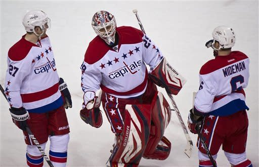 Washington Capitals goalie Tomas Vokou, center, is congratulated by teammates Karl Alzner, left, and Dennis Wideman after shutting out the Montreal Canadiens 3-0 in an NHL hockey game, Saturday, Feb. 4, 2012 in Montreal. (AP Photo/The Canadian Press, Paul Chiasson)