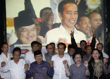 Indonesian presidential candidate Jokowi and his running mate Jusuf celebrate ahead of the official results announcement in South Jakarta