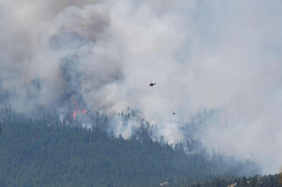 A wildfire burns on 1 July, 2021, outside the British Columbia town of Lytton, which has been gutted by flames.  (REUTERS)