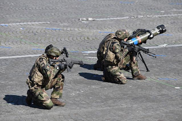 <p>Members of the Section Technique de l'Armee de Terre (Technical Section of the Army) hold German HK 416 assault rifles as they kneel beside an anti-tank missile during the annual Bastille Day military parade on the Champs-Elysees avenue in Paris on July 14, 2017. (Photo: Alain Jocard/AFP/Getty Images) </p>