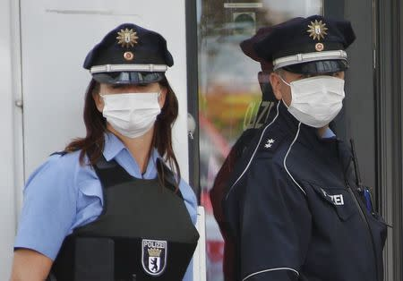 Police officers wearing protective masks stand outside the entrance of a job centre in the Berlin district of Pankow August 19, 2014. REUTERS/Fabrizio Bensch