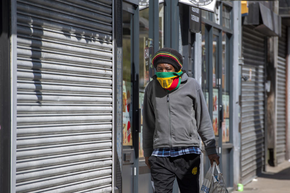 A man uses a scarf as a face mask as he walks past closed shops in Leeds city centre, West Yorkshire on April 14, 2020, as life in Britain continues during the nationwide lockdown to combat the novel coronavirus COVID-19 pandemic. - Britain's economy could shrink by an unprecedented 13 percent this year in the case of a three-month coronavirus lockdown, according to a scenario published Tuesday by fiscal watchdog the Office for Budget Responsibility. (Photo by Anthony Devlin / AFP) (Photo by ANTHONY DEVLIN/AFP via Getty Images)