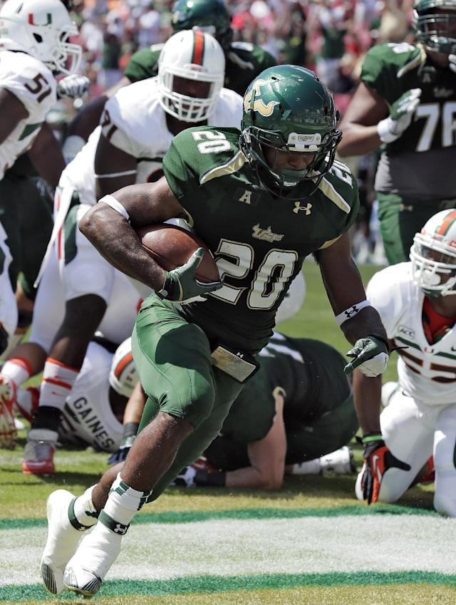 South Florida running back Marcus Shaw (20) runs 3-yards through the Miami defense for a touchdown during the first quarter of an NCAA college football game Saturday, Sept. 28, 2013, in Tampa, Fla. (AP Photo/Chris O'Meara)