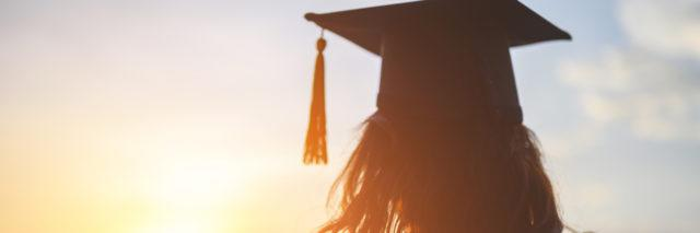 Woman wearing a graduation cap and looking at the sunset