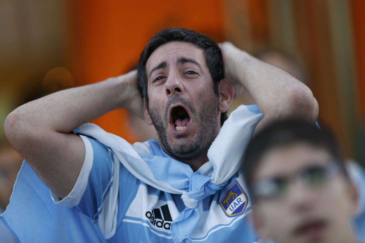 A fan of Argentina reacts while watching a broadcast of the 2014 World Cup final against Germany at the Argentine Embassy in Brasilia, July 13, 2014. REUTERS/Ueslei Marcelino (BRAZIL - Tags: SOCCER SPORT WORLD CUP)