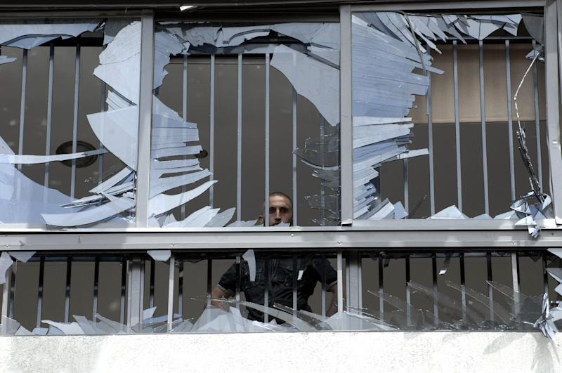 A man peers through a shattered window at the scene of a bombing in the Beir el-Abed, a southern suburb of Beirut, Lebanon, Tuesday, July 9, 2013. A large explosion rocked a stronghold of the Shiite militant Hezbollah group south of the Lebanese capital Tuesday, setting several cars on fire, sending a thick plume of black smoke billowing into the sky and wounding more than a dozen people, security officials said.(AP Photo/Ahmed Omar)
