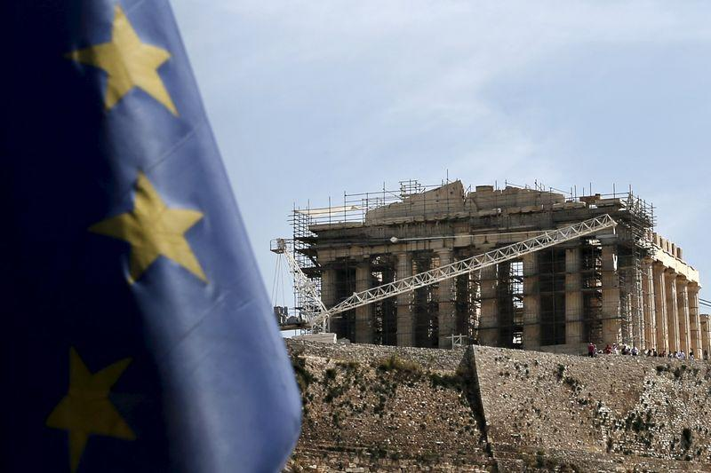 An EU flag flutters as the ancient Parthenon temple is seen in the background in Athens