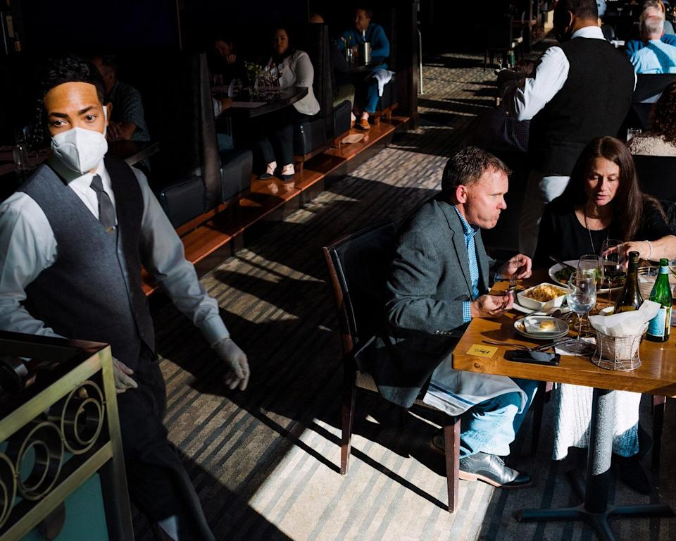 """<div class=""""caption""""> Server Mercury Jackson walks past a couple on a date in the dining room. </div> <cite class=""""credit"""">Photo By DUSTIN CHAMBERS</cite>"""
