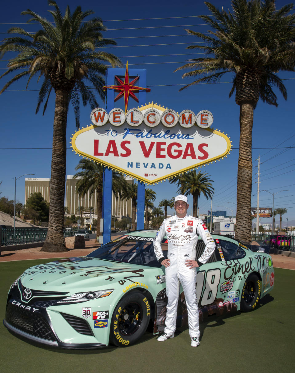 """In this image provided by Ethel M Chocolates, NASCAR driver Kyle Busch poses in front of the famous """"Welcome to Fabulous Las Vegas"""" sign with his Ethel M Chocolates sponsor race car in Las Vegas. Busch first went to the Ethel M candy factory with his grandmother. It wasn't a tourist stop to the young Busch, it was a candy store and his grandmother let him roam the cactus garden and rewarded him with the craft chocolates. Ethel M is part of the Mars Corp., the longtime sponsor of Busch's team. Busch will feature the brand on his car in Sunday's race. (Christian Andrade-Cashman/Ethel M Chocolates via AP)"""