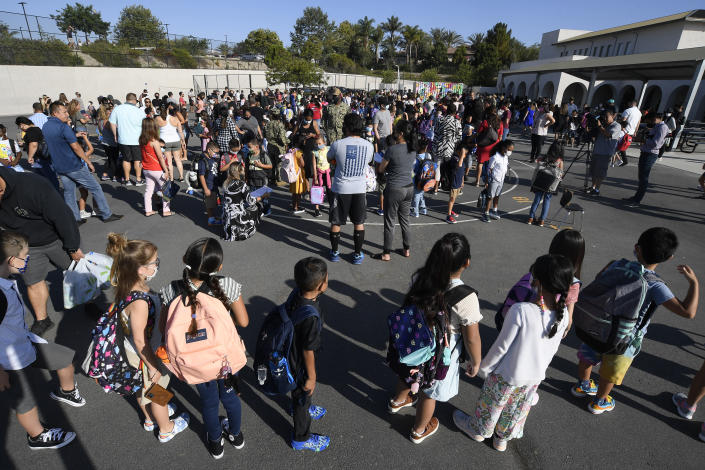 Students and parents wait on the blacktop before the first day of school at Enrique S. Camarena Elementary School, Wednesday, July 21, 2021, in Chula Vista, Calif. The school is among the first in the state to start the 2021-22 school year with full-day, in-person learning. (AP Photo/Denis Poroy)