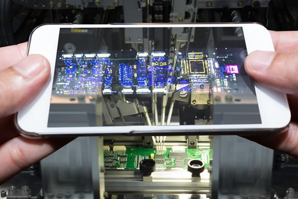 A smartphone scanning a circuit board.