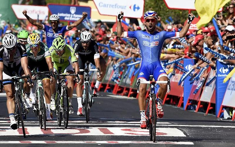 """French cyclist Nacer Bouhanni (R) of FDJ.fr celebrates as he crosses the finish line to win the 2nd stage of the 69th edition of """"La Vuelta"""" Tour of Spain on August 24, 2013"""