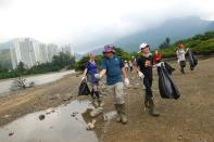 Climate activists Rose Netherton, 36, Lance Lau, 11, and Elise Hon, 11, take part in a climate strike and a beach clean-up with other participants at San Tau Beach on Lantau island in Hong Kong