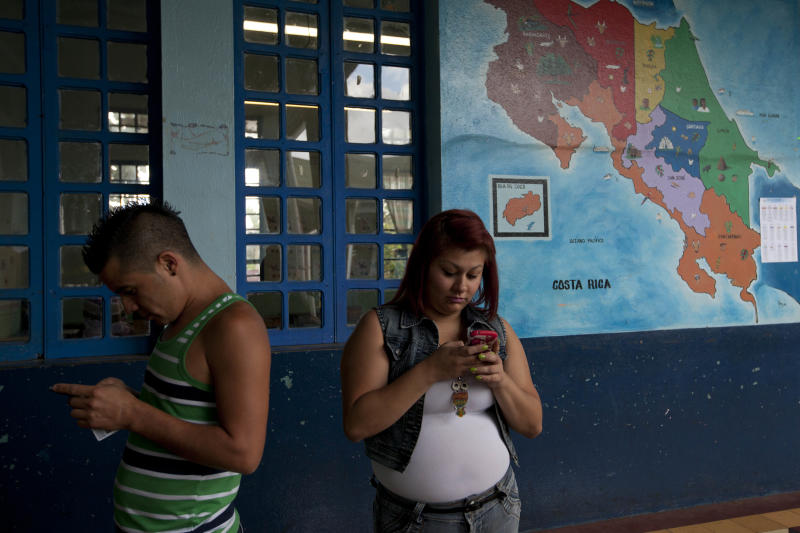 People check their phones as they waits to vote at Republica de la Argentina school in San Jose, Costa Rica, Sunday, Feb. 2, 2014. Presidential elections in two Central American countries Sunday are both referendums on political stagnation, with voters in Costa Rica deciding whether to oust the long-ruling party, and voters in El Salvador deciding whether to bring it back to power. (AP Photo/Moises Castillo)