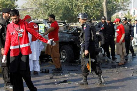 Police and rescue personnel inspect a vehicle damaged by a suicide bomber which killed a senior Pakistani police official on his way to work in Peshawar, Pakistan November 24, 2017. REUTERS/Fayaz  Aziz