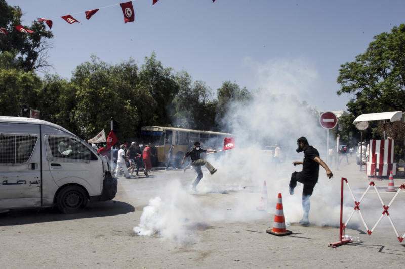 Tunisian opposition politician Mohammed Brahmi's supporters run in the tear gas during clashes with police after the funerals in Tunis, Saturday July, 27, 2013. Mohamed Brahmi was shot 14 times in front of his home within sight of his family on Thursday, plunging the country into a political crisis and unleashing demonstrations around the country blaming the government for the assassination. (AP Photo/Amine Landoulsi)