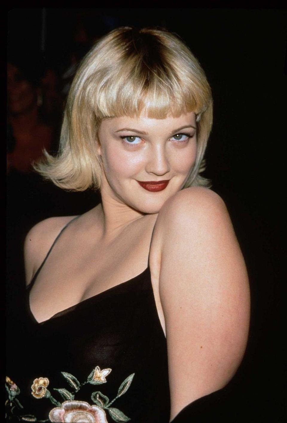 <p>Life of the party Drew Barrymore strikes a seductive pose at the premiere of her film <em>The Wedding Singer</em> in 1998. </p>
