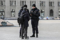 Police officers check documents of a man as they patrol a street to prevent a rally commemorating the founding of Belarus' 1918 proclamation of independence from Russia, in Minsk, Belarus, Thursday, March 25, 2021. Belarusian opposition have urged people to protest against repressions in the country and Lukashenko's regime. (BelaPan via AP)