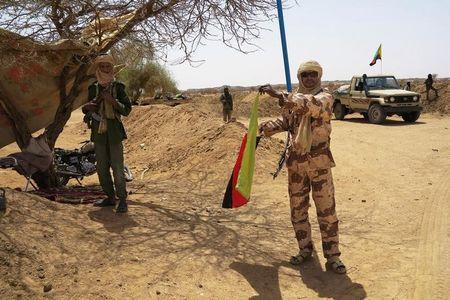 A fighter with the Tuareg separatist group MNLA brandishes a separatist flag for the region they call Azawad outside the local regional assembly in Kidal