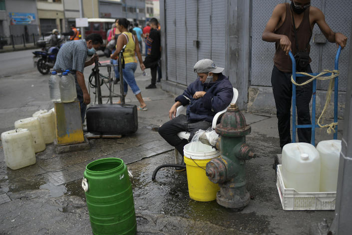 Residents tap into a fire hydrant to fill their containers with water in the San Juan neighborhood of Caracas, Venezuela, Tuesday, Jan. 19, 2021, amid the new coronavirus pandemic. Venezuela's economic crisis has sent millions fleeing and those left behind lacking basic goods, including gasoline, in a country with one of the world's largest proven oil reserves. (AP Photo/Matias Delacroix)