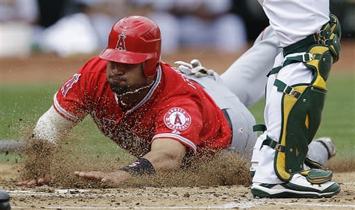 Los Angeles Angels' Albert Pujols slides to score against the Oakland Athletics' in the third inning of a baseball game, Wednesday, Sept. 5, 2012, in Oakland, Calif. Pujols scored on a single by Howie Kendrick. (AP Photo/Ben Margot)