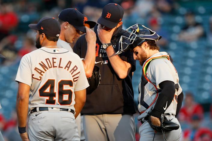 Detroit Tigers pitching coach Chris Fetter, second from right, talks with starting pitcher Matt Manning, second from left, with catcher Eric Haase, right, and third baseman Jeimer Candelario, left, looking on during the second inning of a baseball game against the Los Angeles Angels in Anaheim, Calif., Thursday, June 17, 2021.