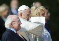 Pope Francis, center, is flanked by Irish President Michael D. Higgins, left, and President's wife Sabina, upon his arrival at the Presidential residence in Dublin, Ireland, Saturday, Aug. 25, 2018. Pope Francis is on a two-day visit to Ireland. (AP Photo/Peter Morrison)