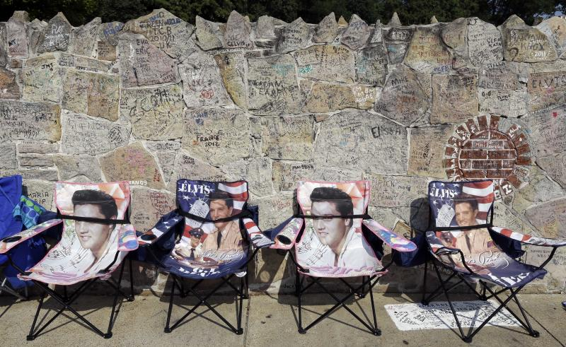 Elvis Presley chairs hold spots for people waiting outside Graceland, Presley's Memphis, Tenn. home, on Wednesday, Aug. 15, 2012. Fans are lined up to take part in the annual candlelight vigil marking the 35th anniversary of Presley's death. (AP Photo/Mark Humphrey)
