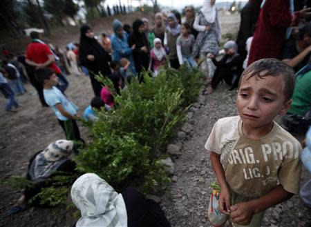 A Syrian refugee boy cries as he attends the funeral of five Free Syrian Army fighters, killed by Syrian security forces near the Idlib province of Syria, in Yayladagi in Hatay province near the Turkish-Syrian border, in this August 4, 2012 file photo. REUTERS/Umit Bektas/Files