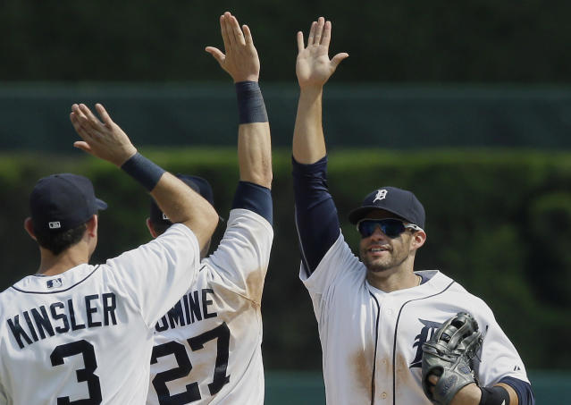 Detroit Tigers left fielder J.D. Martinez, right, celebrates with teammates Ian Kinsler (3) and Andrew Romine (27) after their 5-1 win over the Cleveland Indians in a baseball game, Sunday, July 20, 2014, in Detroit. (AP Photo/Carlos Osorio)