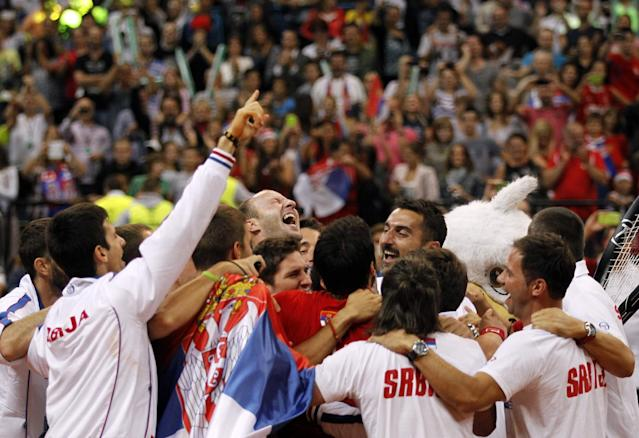 Serbian players celebrate Janko Tipsarevic 's victory after his Davis Cup semifinal tennis match against Vasek Pospisil of Canada, in Belgrade, Serbia, Sunday, Sept. 15, 2013. (AP Photo/Darko Vojinovic)