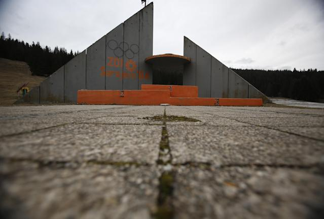 """In this picture taken on Friday, Feb. 21, 2014, a concrete podium for winners with the text """"Winter Olympic Games 1984"""" stands abandoned near jumping hills at Mt. Igman near the Bosnian capital of Sarajevo. Wartime destruction and negligence have turned most of Sarajevo's 1984 Winter Olympic venues into painful reminders of the city's golden times. The world came together in the former Yugoslavia in 1984 after the West had boycotted the 1980 Olympics in Moscow and Russia boycotted the 1984 Summer Games in Los Angeles. Just eight years later, the bobsleigh and luge track on Mount Trbevic was turned into an artillery position from which Bosnian Serbs pounded the city for almost four years. Today, the abandoned concrete construction looks like a skeleton littered with graffiti. (AP Photo/Amel Emric)"""