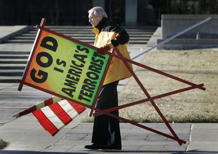 FILE - In this July 1, 2007 file phtoo, the Rev. Fred Phelps Sr. prepares to protest outside the Kansas Statehouse in Topeka, Kan. Phelps, the founder of the Kansas church known for anti-gay protests and pickets at military funerals, died Thursday, March 20, 2014. He was 84. (AP Photo/Orlin Wagner, File)