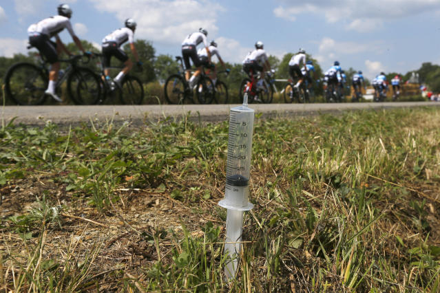 Team Sky passes one of several syringes which were put on the side of the road during the fourth stage of the Tour de France cycling race over 195 kilometers (121 miles) with start in La Baule and finish in Sarzeau, France, Tuesday, July 10, 2018. (AP Photo/Peter Dejong)