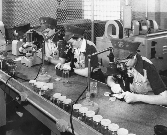 FILE - In this Feb. 10, 1943, file photo, employees of International Harvester inspect ball bearings in Chicago, the smallest being one eighth of an inch in diameter. The bearings must be sorted according to size within 25 millionths of an inch. Not since World War II when factories converted from making automobiles to making tanks, Jeeps and torpedos has the entire nation been asked to truly sacrifice for a greater good. (AP Photo, File)