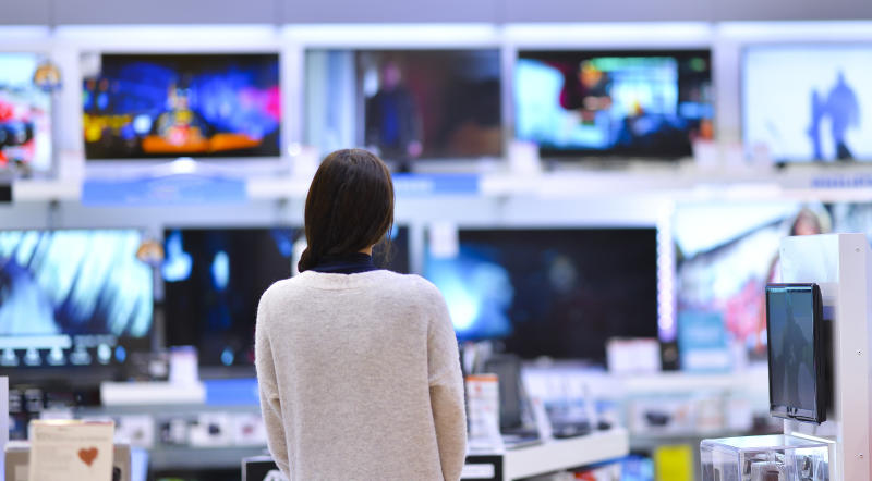 A woman looking at a wall of televisions