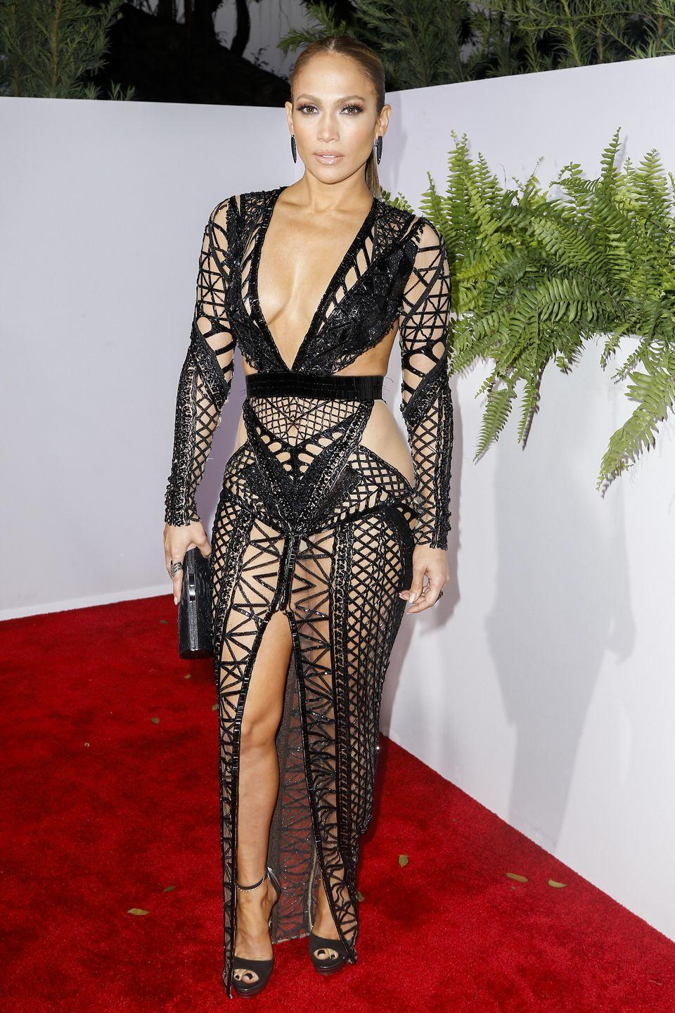 <p>One night, multiple jaw-dropping outfits...I guess that's J.Lo for ya! Here she is still at the Billboard Latin Music Awards in Coral Gables, Florida wearing another plunging dress. But this time it's black, strappy, and perforated all over. </p>