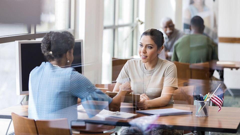 The mature adult African American bank officer helps the Hispanic mid adult female soldier understand the terminology in the loan application form.