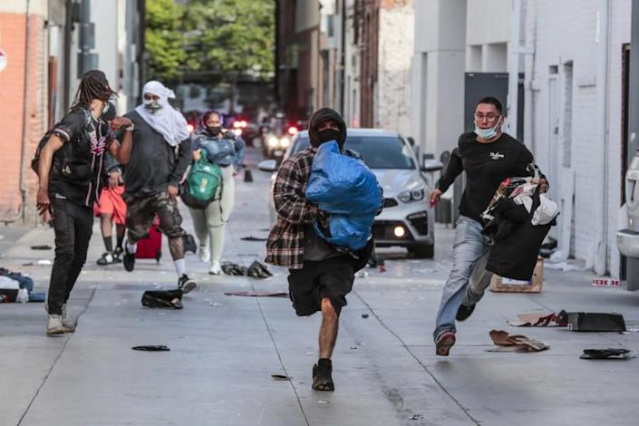 "Looters rush away from police after picking through a store in downtown Santa Monica on Sunday. <span class=""copyright"">(Robert Gauthier/Los Angeles Times)</span>"