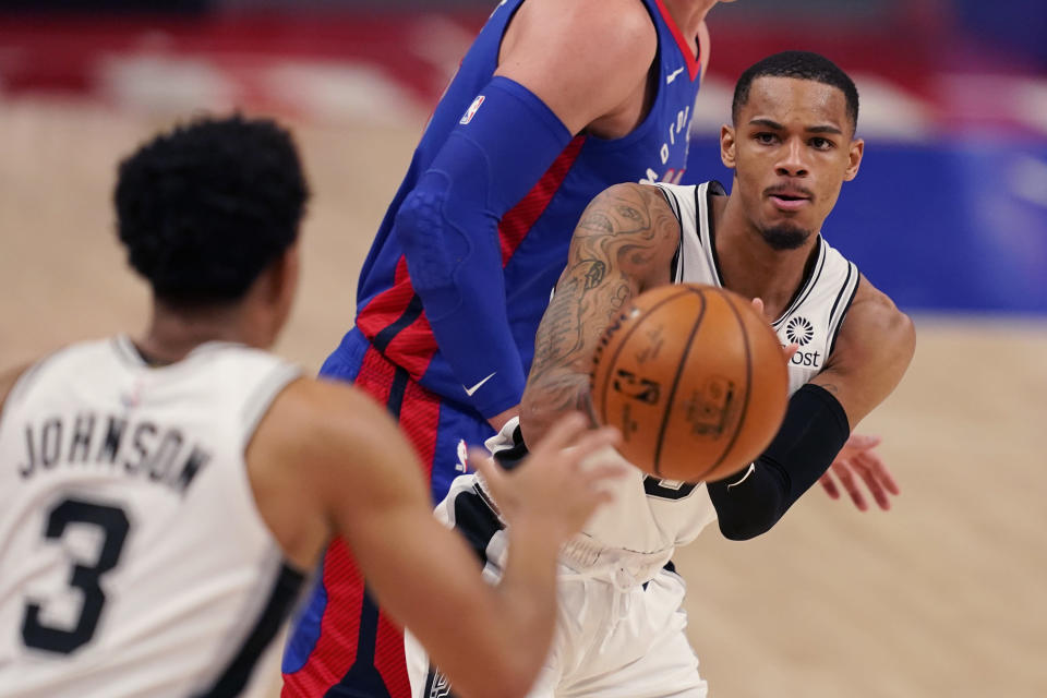 San Antonio Spurs guard Dejounte Murray passes to forward Keldon Johnson (3) during the second half of an NBA basketball game against the Detroit Pistons, Monday, March 15, 2021, in Detroit. (AP Photo/Carlos Osorio)